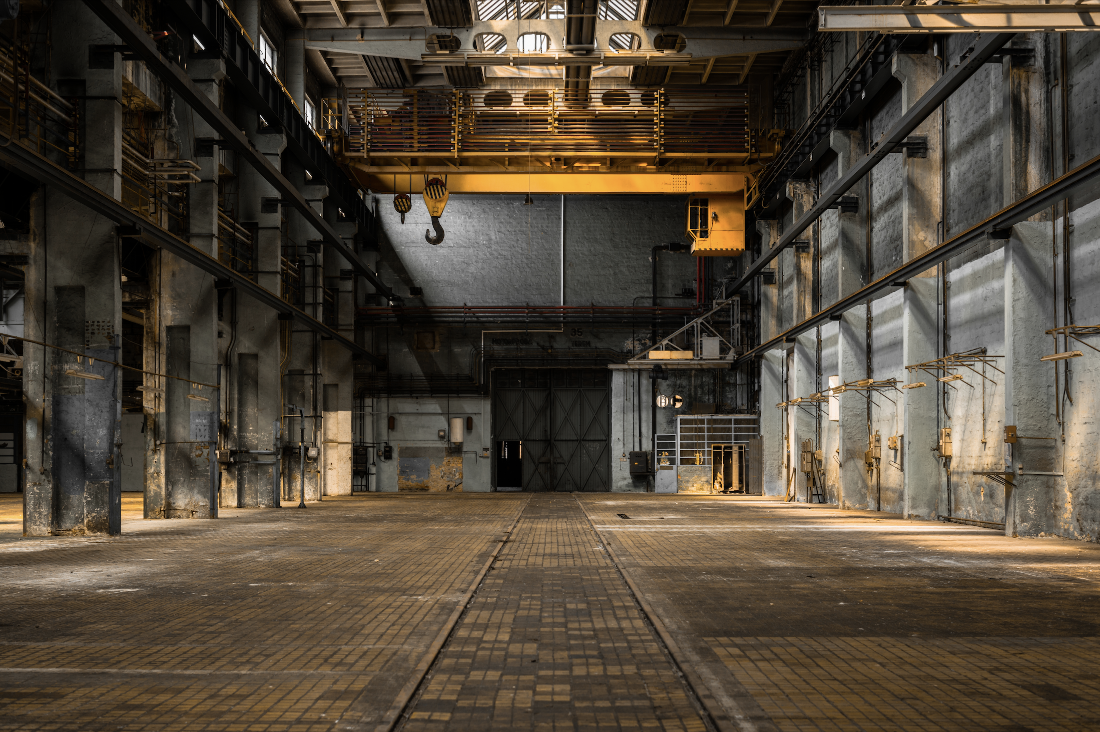 A inside view photo of a very cool old heavy industrial warehouse with crane service.